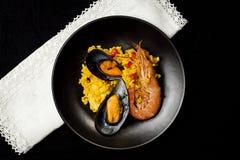 Traditionella ris i paella med fisken och kött Arkivfoto