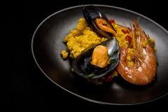 Traditionella ris i paella med fisken och kött Arkivfoton