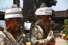 Traditionella skulpturer för Balinese med den röda vit bandanaen för framsidor och Arkivbilder