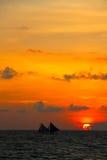 Traditionella två seglar fartyg fångar de sista glimpsna av solnedgången Arkivfoto