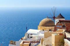 Traditionelle Architektur mit Windmühle von Oia-Stadt am sonnigen Tag, Santorini-Insel, Griechenland Stockfotografie
