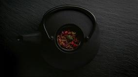 Traditionelle asiatische Teezeremonieanordnung Eisenteekanne, Schalen, Trockenblumen stockfoto