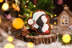 Traditionelle Bäckerei des Feiertags Nahrungsmittel Lebkuchen wenig pinguin im Weihnachtshut mit Geschenk in der gemütlichen warm stockfotos