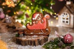 Traditionelle Bäckerei des Feiertags Nahrungsmittel Lebkuchenweihnachtsbär im Pferdeschlitten in der gemütlichen Dekoration mit G lizenzfreie stockfotos
