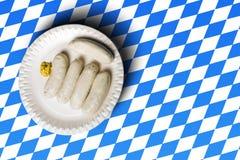Traditionelle bayerische Würste auf weißer Platte und bayerischer Flagge Stockfotografie