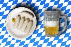 Traditionelle bayerische Würste auf weißer Platte und Bier in vorderem O Lizenzfreies Stockbild