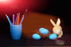 Traditionelle blaue Eier im Nest und im Becher mit Bleistiften und Bürste Stockbilder