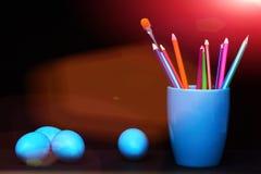 Traditionelle blaue Eier und Becher mit Bleistiften und Bürste Stockbilder