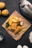 Traditionelle britische Fisch und auf der dunklen Oberfläche Lizenzfreie Stockfotos