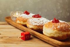 Traditionelle Donuts für jüdischen Feiertag Chanukka Selektiver Fokus auf dem Donut in der Mitte Lizenzfreies Stockbild