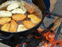 Traditionelle ecuadorian süße Nahrung - Käse Empanadas kochte auf offenem Feuer im großen Topf mit Öl lizenzfreies stockfoto