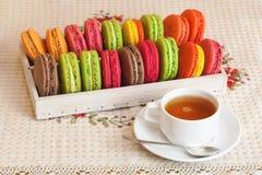 Traditionelle französische bunte macarons in einem Kasten, Tasse Tee Lizenzfreie Stockfotografie