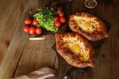 Traditionelle georgische Teller Khachapuri Adjara Gebackenes Brot angef?llt mit K?se und Eiern stockfotos