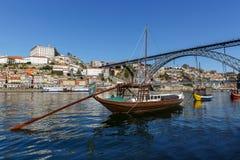Traditionelle hölzerne Boote in dem Duero-Fluss für das Transportieren des Weins mit der Brücke Dom Luis Lizenzfreie Stockfotografie