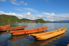 Traditionelle hölzerne Boote, die in den Lugu See, Yunnan, China schwimmen Lizenzfreie Stockfotos