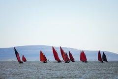 Traditionelle hölzerne Boote mit rotem Segel Stockbilder