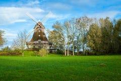 Traditionelle hölzerne Windmühle in einem üppigen Garten Stockbilder