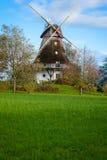 Traditionelle hölzerne Windmühle in einem üppigen Garten Stockfotografie
