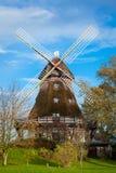 Traditionelle hölzerne Windmühle in einem üppigen Garten Lizenzfreies Stockbild