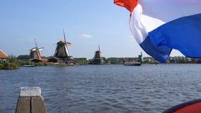 Traditionelle Holland Windmills und sich hin- und herbewegende Flagge in Zaanse Schans, die Niederlande Touristisches Dorf nahe d stock video