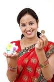 Traditionelle indische Frau, die ein Sparschwein hält Lizenzfreie Stockfotos