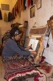 Traditionelle islamische Frau, die an einer Wolldecke arbeitet Lizenzfreies Stockbild