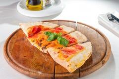 Traditionelle italienische geschlossene Pizza Calzone auf dem hölzernen Brett auf der gedienten Restauranttabelle Selektiver Foku Stockbilder