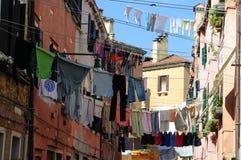 Traditionelle italienische Straße mit der Kleidung, die heraus hängt, um betwe zu trocknen Stockfotografie