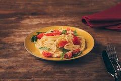 traditionelle italienische Teigwaren mit Tomaten und Arugula in der Platte Stockfotos