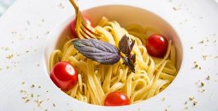 Traditionelle italienische Teigwaren mit Tomaten und Basilikum in der Platte mit Gabel Lizenzfreies Stockfoto