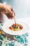 Traditionelle italienische Teigwaren mit Tomaten und Basilikum in der Platte mit Gabel Stockbilder