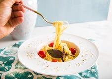Traditionelle italienische Teigwaren mit Tomaten und Basilikum in der Platte mit Gabel Stockfotografie