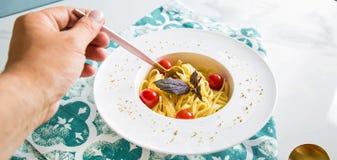 Traditionelle italienische Teigwaren mit Tomaten und Basilikum in der Platte mit Gabel Lizenzfreie Stockfotografie