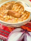 traditionelle Küchebohnen mit Wurst und roter Zwiebel Stockfoto