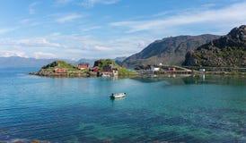 Traditionelle Kabinen von fishmen und ein Boot im Meer bellen, Finnmark, Norwegen Lizenzfreie Stockfotos
