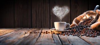 Traditionelle Kaffeetasse mit Herz-förmigem Dampf lizenzfreie stockbilder