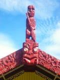 Traditionelle Maori- geschnitzte marae auf Hausdach in der roten Farbe unter blauem Himmel Stockfotos