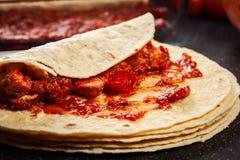 Traditionelle mexikanische Enchiladas der Vorbereitung mit Hühnerfleisch, würziger Tomatensauce und Käse Lizenzfreie Stockfotografie
