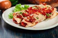 Traditionelle mexikanische Enchiladas mit Hühnerfleisch, würziger Tomatensauce und Käse auf einer Platte Stockfotos