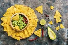 Traditionelle mexikanische Nahrung, Nachos und Guacamolesoße auf rustikalem Hintergrund Draufsicht, flache Lage stockbilder
