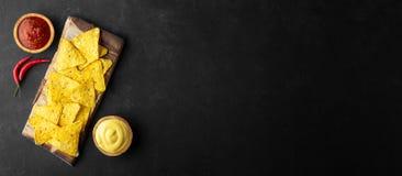 Traditionelle mexikanische Nahrungsmittelcorn chipe Nachos mit Salsa- und Käsesoße auf schwarzem Hintergrund stockfotografie