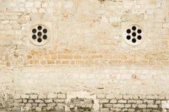 Traditionelle Mittelmeersteinwand mit zwei kleinen runden Steinfenstern lizenzfreie stockfotografie