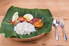 Traditionelle nasi lemak Küche auf Bananenblatt mit gebratenem Huhn Lizenzfreies Stockfoto