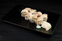 Traditionelle neue japanische Sushirollen auf einem schwarzen Hintergrund Lizenzfreies Stockbild