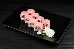 Traditionelle neue japanische Sushirollen auf einem schwarzen Hintergrund Lizenzfreies Stockfoto