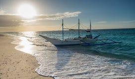 Traditionelle philippinische asiatische Fährentaxi-Ausflugboote auf puka setzen i auf den Strand Stockfotografie