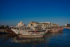 Traditionelle qatari Dhowboote mit den Skylinen von Westbuchtwolkenkratzern, genommen bei Sonnenuntergang Doha, Qatar lizenzfreie stockbilder
