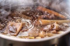 Traditionelle Rinderbrühe mit Gemüse, den Knochen und den Bestandteilen im Topf, Rezept kochend Lizenzfreie Stockfotografie
