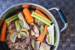 Traditionelle Rinderbrühe mit Gemüse, den Knochen und den Bestandteilen im Topf, Rezept kochend Stockfotos