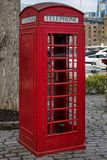 Traditionelle rote englische Telefonzelle, die nach rechts gegenüberstellt Stockfotografie